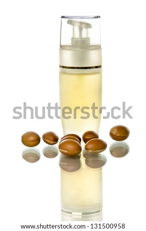 Bottle of argan oil with fruits on a white background and reflection - stock photo
