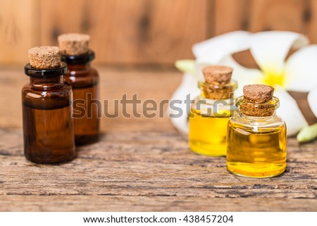 bottle of aroma essential oil or spa or natural fragrance oil with dry flower on wooden table, spa or alternative meditation aroma  - stock photo