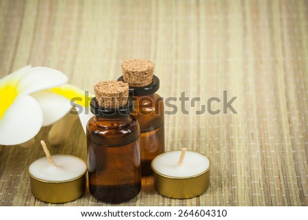 bottle of aroma essential oil with flower and candle on wooden background, spa concept.