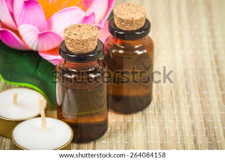 bottle of aroma essential oil with lotus flower and candle on wooden background, spa concept. - stock photo