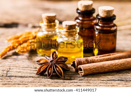 bottle of aroma essential oil with star anise with cinnamon stick with dry flower on  on grunge wooden table , spa  and alternative medical concept.