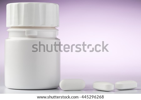 Bottle of aspirin drugs and three pills in the foreground - stock photo