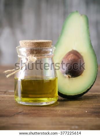 bottle of avocado essential oil with fresh avocado fruit closeup - stock photo