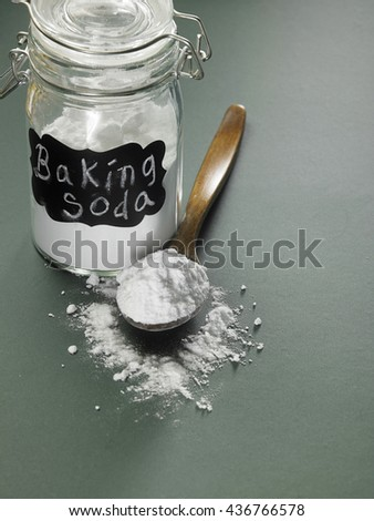 bottle of baking soda with wooden spoon