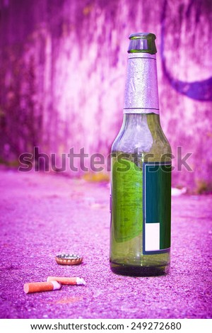 Bottle of beer resting on the ground with three cigarette's butts.Alcoholism and tobacco addiction concept - toned image - stock photo