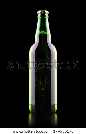 Bottle of beer with drops on a black
