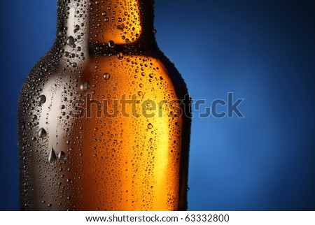 Bottle of beer with drops on a blue background. Close up part of the bottle.