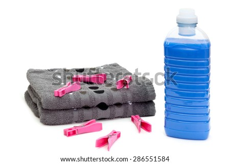 Bottle of blue laundry detergent near stack of towels with clothespins - stock photo