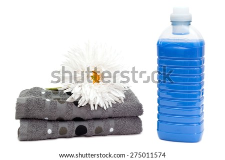 Bottle of blue laundry detergent near towels with a white flower - stock photo