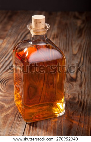 Bottle of brandy on a wooden table - stock photo