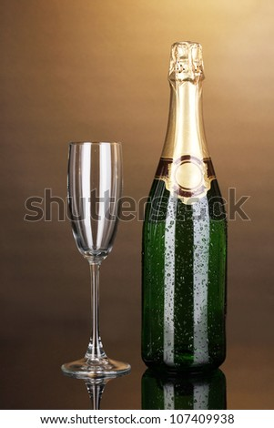 Bottle of champagne and goblet on brown background - stock photo