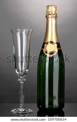 Bottle of champagne and goblet on grey background - stock photo