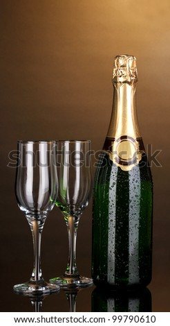 Bottle of champagne and goblets on brown background - stock photo