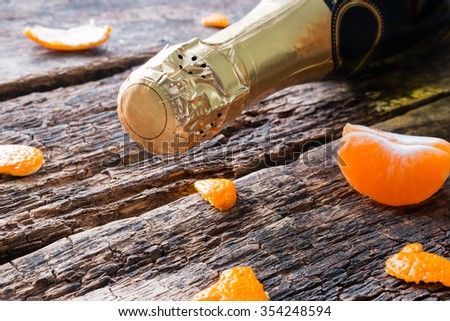 bottle of champagne and tangerines on a wooden background - stock photo