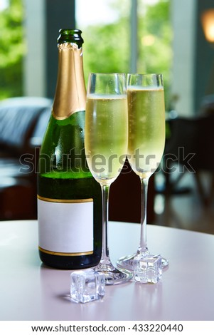 bottle of champagne and two glasses on the table - stock photo