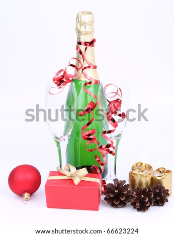 Bottle of champagne, glasses, candles, christmas ball, a gift and cones - stock photo