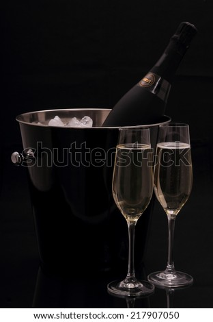 Bottle of champagne in bucket and two glasses on black background - stock photo