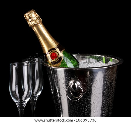 Bottle of champagne in bucket isolated on black - stock photo