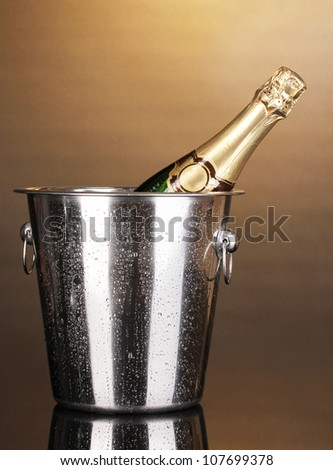 Bottle of champagne in bucket on brown background - stock photo