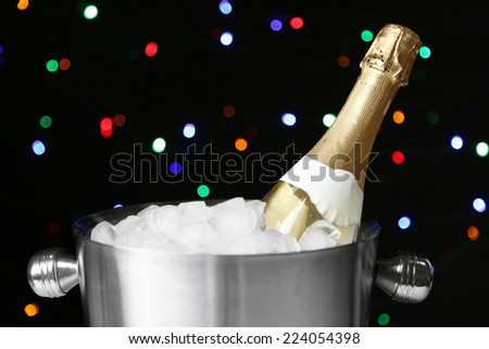 Bottle of champagne in bucket with ice, on black background with color lights - stock photo