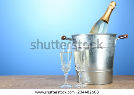Bottle of champagne in metal ice bucket and two glasses on wooden table on color background - stock photo