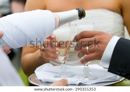 bottle of champagne pooring in to glasses