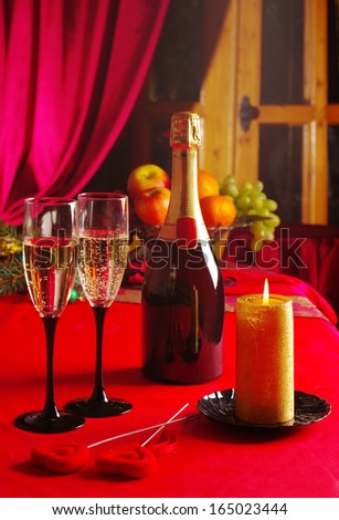 Bottle of champagne, two glasses and burning candle