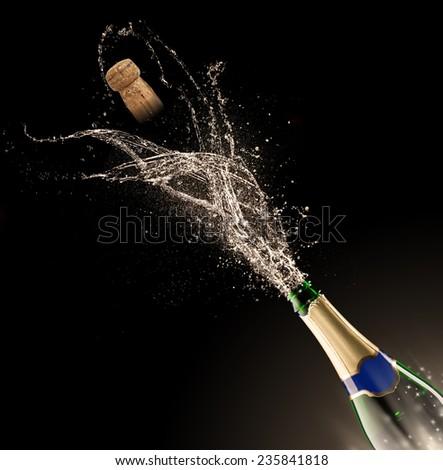 Bottle of champagne with splash isolated on black background - stock photo