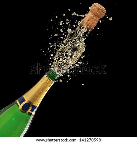 Bottle of champagne with splash on black background - stock photo