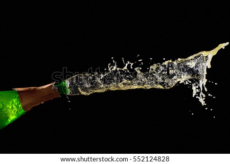 Bottle of champagne with splashes isolated on black.