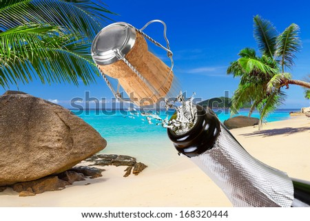 Bottle of champagne with splashes on the tropical beach - stock photo