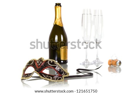 Bottle of champagne with two flutes and party mask - stock photo