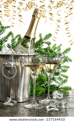 bottle of champagne with two glasses and festive golden streamer decoration - stock photo