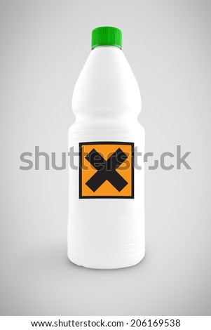 Bottle of chemical liquid with hazard symbol for harmful or irritant content - stock photo