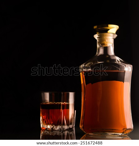 Bottle of cognac on black background - stock photo