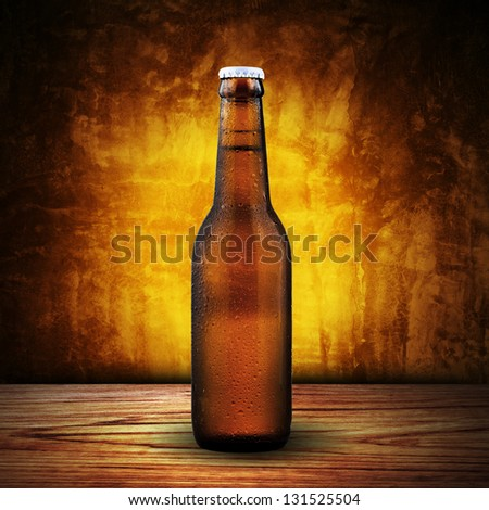 Bottle of cold beer on wood table with yellow grunge background - stock photo