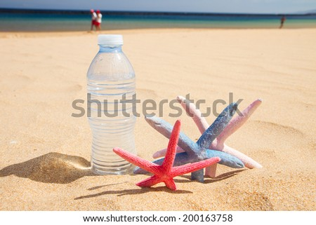 bottle of cool water with starfish on sandy beach - stock photo