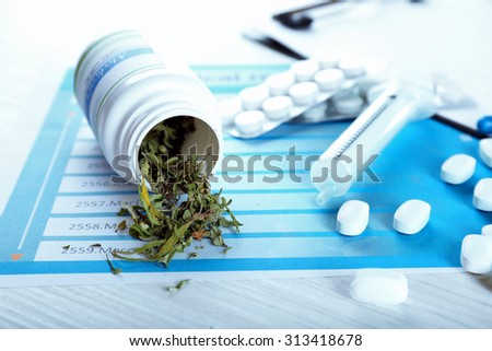 Bottle of dry medical cannabis and pills with clipboard on table close up - stock photo