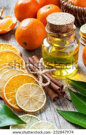 Bottle of essential citrus oil, dried orange and lemon slices, cinnamon sticks and ripe tangerines on old table. - stock photo