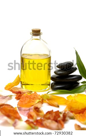 bottle of essential oil and black Stones balanced stones  with colorful flower plants - stock photo