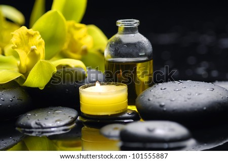 bottle of essential oil and branch yellow orchid with candle on zen stones