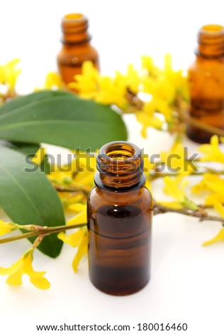 Bottle of essential oil and flowers isolated on white background - stock photo