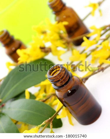 Bottle of essential oil and flowers on white background - stock photo