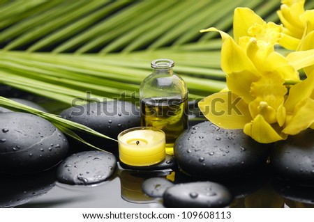 bottle of essential oil and green leaf with orchid and candle on pebbles