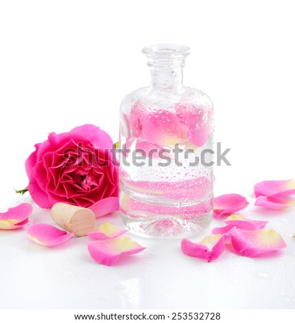 Bottle of essential oil and pink rose isolated on white - stock photo