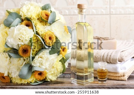 Bottle of essential oil, bouquet of yellow carnation flowers in the background - stock photo