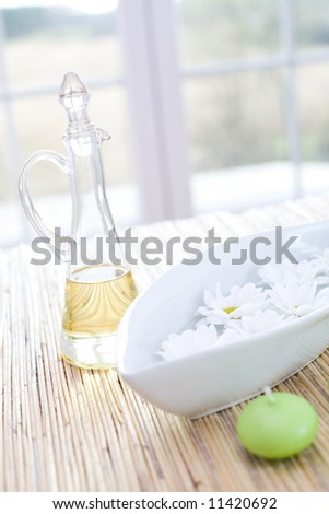Bottle of essential oil, candle and fresh flowers / in the beauty salon