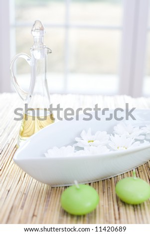 Bottle of essential oil, candles and fresh flowers / in the beauty salon