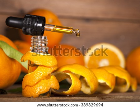 Bottle of essential oil from oranges on wooden background - alternative medicine - stock photo