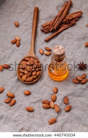 Bottle of extra virgin almonds oil with whole almonds and cinnamon sticks on hemp sack background. - stock photo